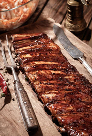 Delicious BBQ ribs with coleslaw on wooden table.