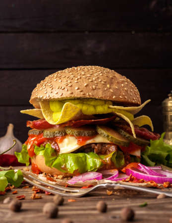 Tasty burger with guacamole and nachos on a wooden table