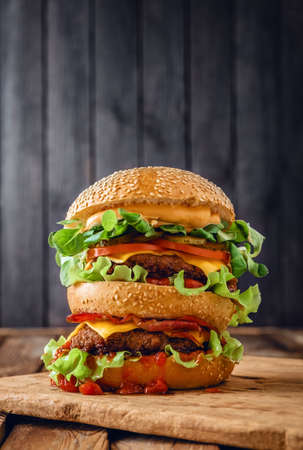 Home made double burger on wooden background. Copyspace for text.