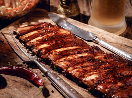 Delicious BBQ ribs with coleslaw and beer on wooden table.