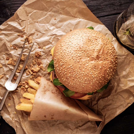 classic burger: Classic burger and chips on the wooden table. Top view. Stock Photo