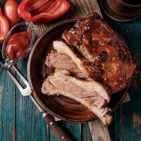 country kitchen: Delicious barbecued ribs seasoned with a spicy basting sauce and served with chopped fresh vegetables on an old rustic wooden chopping board in a country kitchen. Top view.
