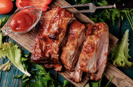 Delicious barbecued ribs seasoned with a spicy basting sauce and served with chopped fresh vegetables on an old rustic wooden chopping board in a country kitchen. Top view.
