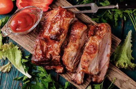 grilled pork: Sườn nướng ngon ướp với nước sốt cay Phết và ăn kèm với rau tươi xắt nhỏ vào một mộc mạc thớt gỗ cũ trong một nhà bếp nước. Top xem. Kho ảnh