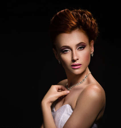headshoot: Portrait of a beautiful ginger woman in the image of the bride. Dark background. Stock Photo
