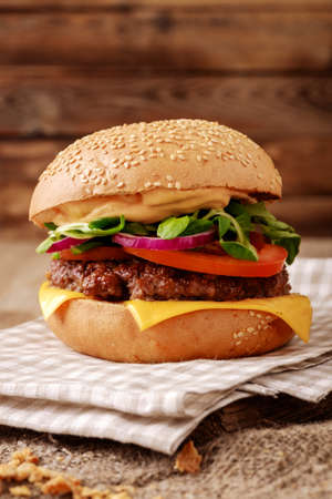burger: Closeup of home made burger on wooden background. Stock Photo
