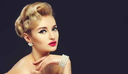 sixties: Beautiful young girl with jewels. Make-up in sixties style arrow. Retro Hairstyle.