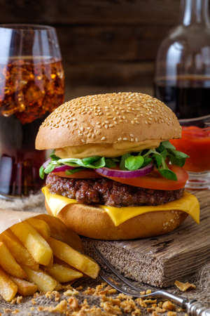 Delicious burger with chips and soda on wooden table Stock Photo