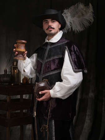 period costume: A man in period costume and hat raises a glass of wine.