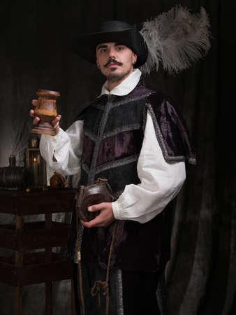 vestidos de epoca: Un hombre con traje de época y un sombrero levanta una copa de vino.