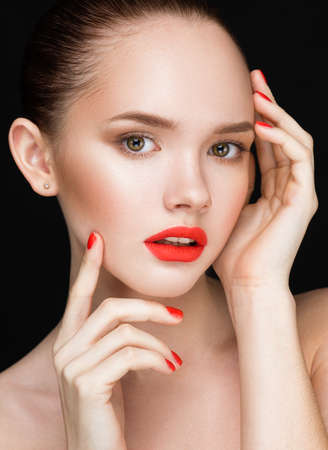 color model: Beautiful woman face closeup over black background. Beautiful Perfect Lips. Beauty model Girl with Red Lips and Nails closeup. Manicure and Makeup. Make up concept. Looking at camera.