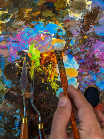 Hand of artist with a paintbrush. The color palette close up.