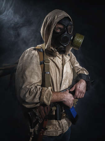 gasmask: Armed man in protective mask. Stalker. Post-apocalyptic fiction