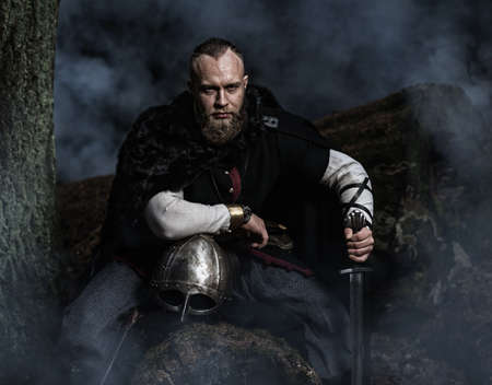 Viking with sword and helmet on a background of smoky forest. Warrior resting. Historic costume.