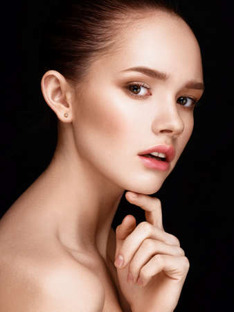 Primer plano de la bella joven con la piel sana clara. Mirando a la cámara. Tocar su cara. Belleza tiro del estudio.