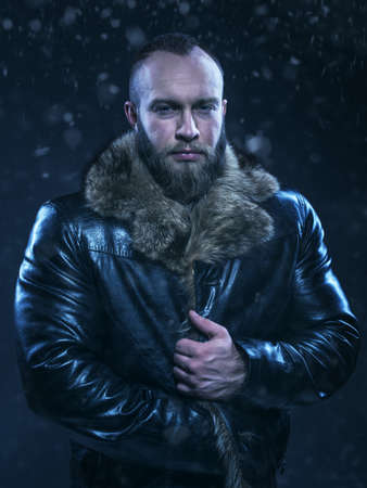 Brutal handsome glum unshaven man with long beard and moustache in black fur coat with collar. Beautiful Luxury Winter Man on snow background