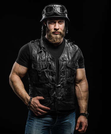 Portrait Handsome Bearded Biker Man in Leather Jacket and Helmet over Black Background Stock Photo