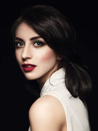 Closeup portrait of elegant young woman over dark background Stock Photo