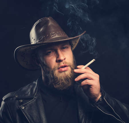cowboy beard: Smoking man with a beard and mustache wearing a cowboy hat. Toned image. Stock Photo