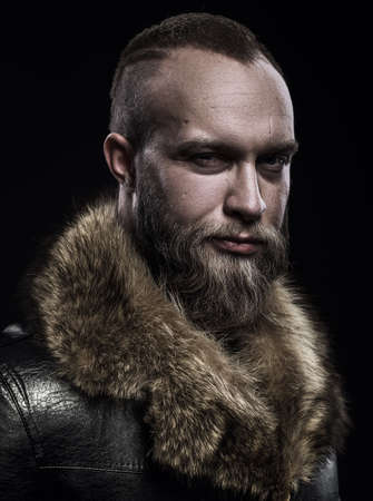 brutal: Brutal handsome glum unshaven man with long beard and moustache in black fur coat with collar