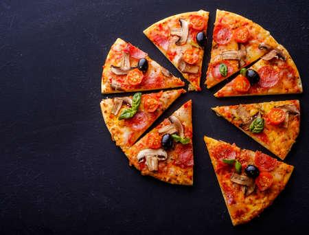 mushroom: Cortar en rodajas deliciosa pizza fresca con las setas y los salchichones en un fondo oscuro. Vista superior. Copyspace.