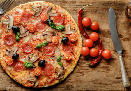 cheese pizza: Delicious fresh pizza with mushrooms, cherry and pepperoni served on wooden table