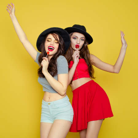 sings: Two young smiling pretty beautiful girls wearing hats holding candies. Studio portrait of two cheerful sexy women over yellow background.