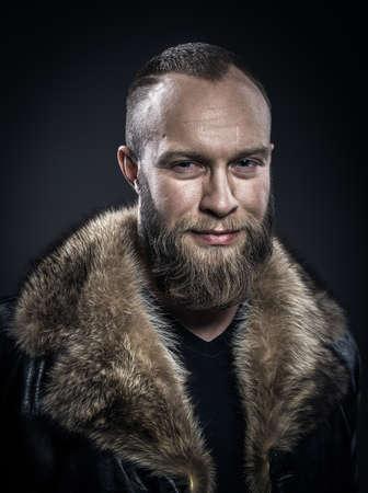 beau jeune homme: Brutal bel homme mal rasé souriant avec une longue barbe et la moustache en manteau de fourrure noire avec col