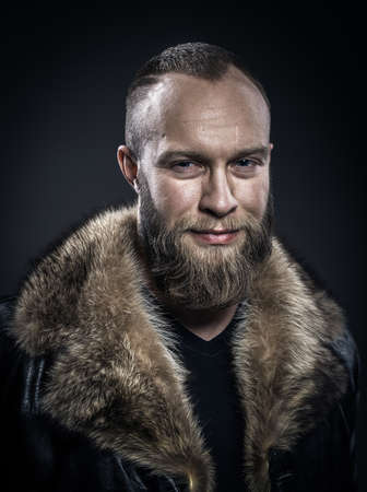 black fashion model: Brutal handsome smiling unshaven man with long beard and moustache in black fur coat with collar Stock Photo