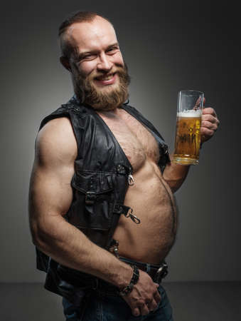 1 man: Smiling biker with beer belly. Man drinks beer from a mug.