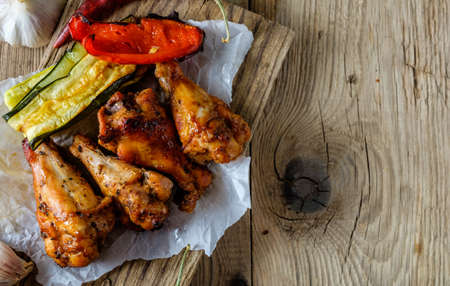 barbeque: BBQ Wings in sauce with Vegetables on a Wooden Table in a Rustic Style. Copyspace.