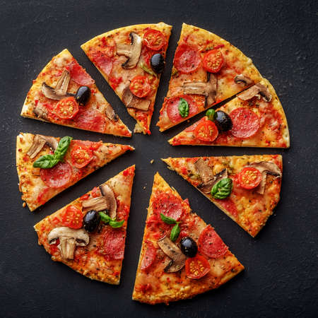 slice pizza: Cut into slices delicious fresh pizza with mushrooms and pepperoni on a dark background. Top view .