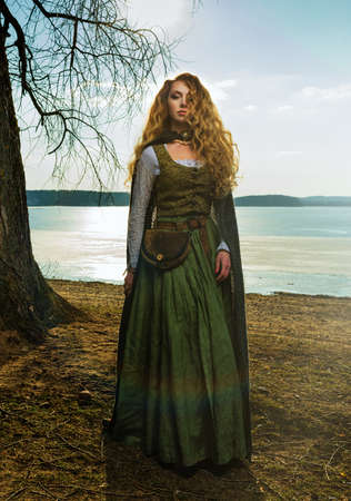 Woman with long curly hair on the lake. Green historical dress.