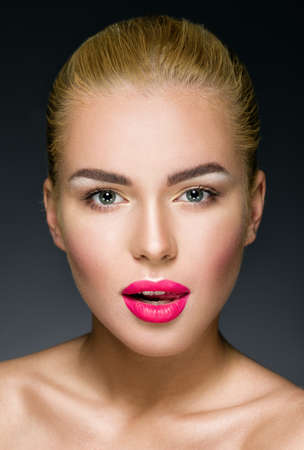 headshot: Beautiful blonde with colorful pink lips looking at the camera. Studio shot over dark background. Seductive woman face.