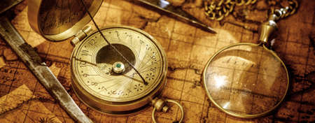 Old vintage retro compass, measuring devices and magnifying glass on ancient world map. Vintage still life.