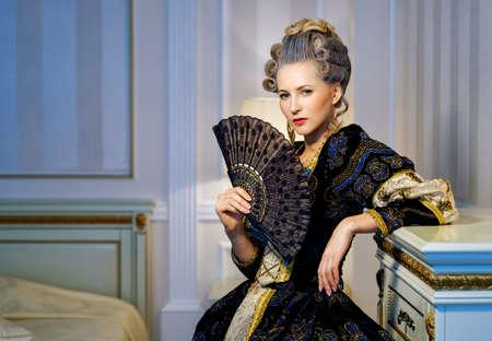 バロック様式のインテリアで歴史的なドレスでファンの美女 写真素材