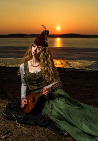 vestido medieval: Chica en vestido medieval y el sombrero en la orilla del lago con un laúd. La puesta del sol.