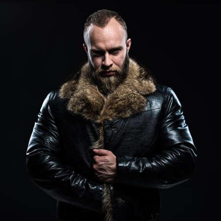 glum: Brutal handsome glum unshaven man with beard and moustache in black fur coat with collar over dark background.