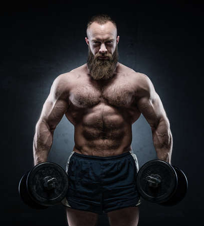 abdominal wall: Bearded Muscular bodybuilder posing with heavy dumbbells on grunge background. Stock Photo