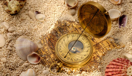 brujula antigua: concepto del mar. Antigua br�jula en la arena con conchas marinas. Antiguo mapa del mundo.