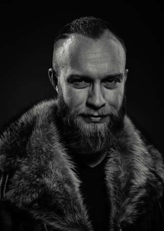 explorer man: Black and white portrait of brutal handsome smiling unshaven man with long beard and moustache in fur coat with collar. Polar explorer. Stock Photo
