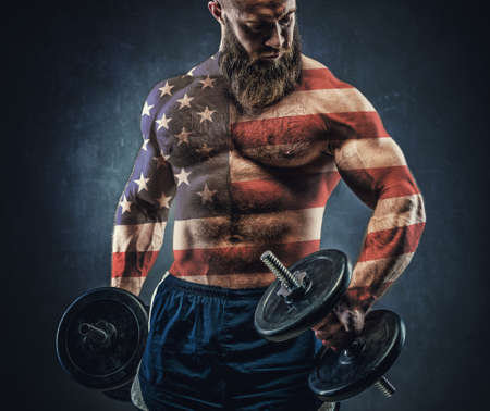 Power athletic bearded man in training pumping up muscles with dumbbell. The body is depicted an American flag. Concept: Captain America. Stock Photo