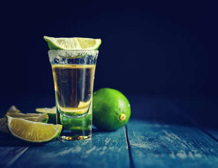silver bars: Mexican Gold Tequila with lime and salt on dark table. Toned. Retro style vintage color. Copyspace for text. Stock Photo