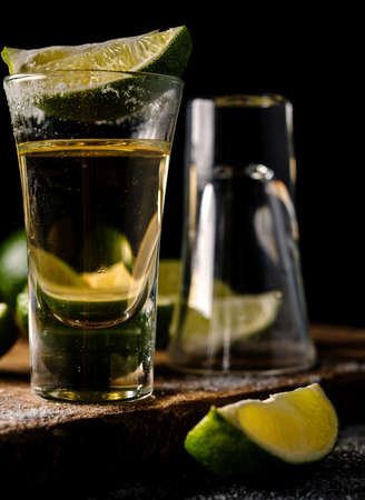 tequila: Gold tequila shot with lime. Gold Mexican tequila. Alcohol drink. Stock Photo