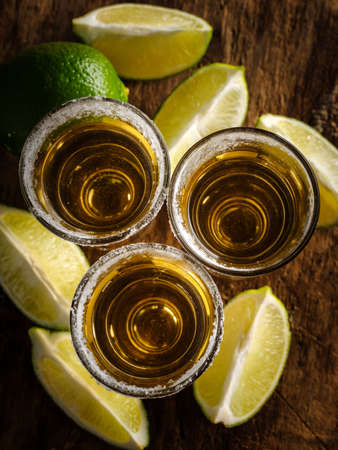 Gold tequila shot with lime on wooden background, selective focus. Top view.