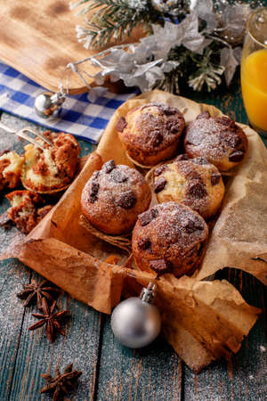 decorate: Chocolate muffins with powdered sugar on the wooden table, rustic style. New Years Concept. Stock Photo