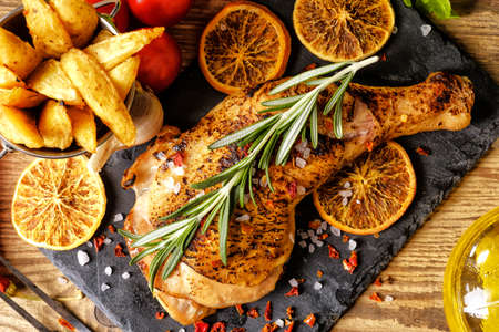 Grilled chicken leg, French fries and orange. Horizontal view from above.