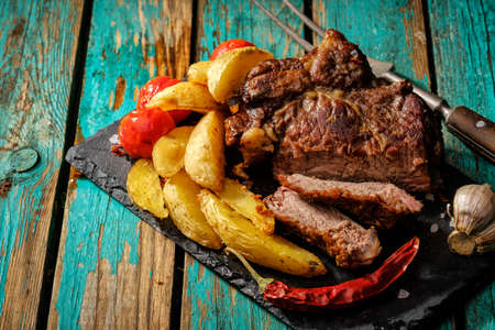 Juicy steak well done beef with potatos and tomatos.