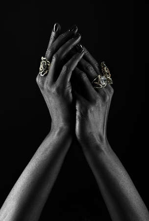 african american woman silhouette: Dark-skinned hand with jewelry on a black background. Hands close up of young woman with black manicure with rings. Luxury lifestyle.