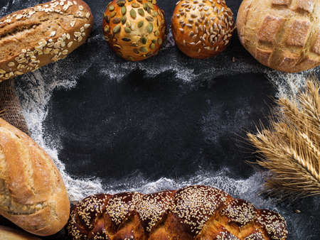 Assortment of fresh bread on the dark table. Copyspace for text. Stock Photo